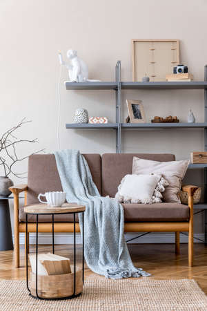 Modern interior design of living room with brown wooden sofa, gray bookstand, vase with flowers, coffee table, decoration and elegant accessories. Beige and japandi concept. Stylish home staging.