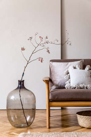 Modern interior design of living room with brown wooden sofa, pillows, rattan basket, glassy vase with flowers and elegant accessories. Beige and japandi concept. Stylish home staging. Template.