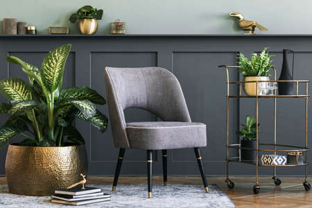 Stylish and modern composition of living room with design gray armchair, gold liquor cabinet, plants and elegant personal accessories. Gray wall panelling with shelf. Modern home decor. Template. Archivio Fotografico