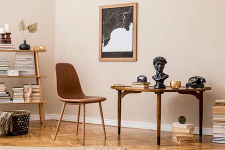 Stylish interior design of private library room with mock up poster map, brown chair, wooden table, bookstand, books and elegant personal accessories. Retro vintage home decor. Beige wall. Template. Zdjęcie Seryjne