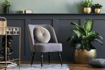 Stylish and modern composition of living room with design gray armchair, gold liquor cabinet, plants and elegant personal accessories. Gray wall panelling with shelf. Modern home decor. Template.