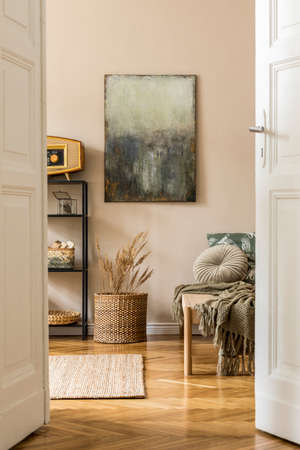 Interior design of oriental style living room with modern chaise longue, shelf, rattan basket, retro radio, flowers and elegant personal accessories. Mock up paintings on the beige wall. Template 写真素材