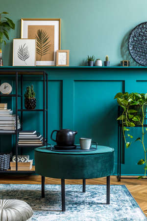 Interior design of living room with design pouf, shlef, basket, carpet and elegant personal accessories. Green wood paneling. Modern home decor. Archivio Fotografico