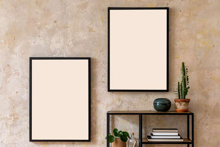 Modern composition of living room interior with black mock up poster frames, bookstand, plant and personal accessories. Stylish home decor. Grunge wall. Wabi sabi concept. Template.