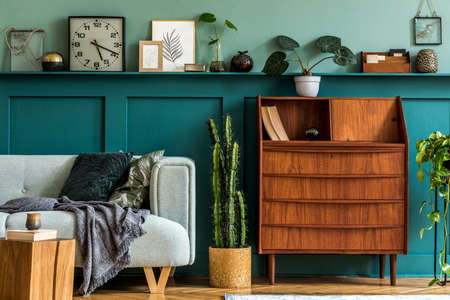 Stylish composition of living room interior with retro wooden cabinet, mint sofa, pillows, plaid, cacti, plants, decoration on the shelf and elegant personal accessories. Vintage home decor. Template
