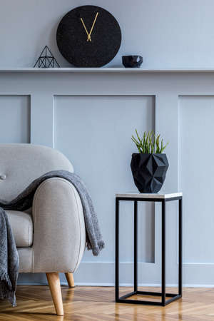 Stylish scandinavian interior of living room with gray sofa, plaid, black clock, wood paneling with shelf, marble stool, plants and elegant personal accessories in design home decor.