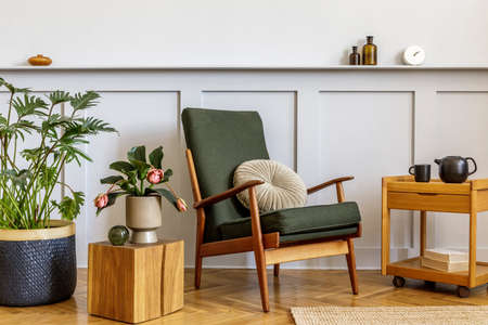 Interior design of stylish living room with vintage green armchair, wooden coffee table, furniture, gray wall, shelf, carpet, plants, clock, book, copy space and elegant personal accessories.