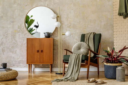 Modern retro composition of living room interior with design armchair, pouf, tea pot on the tray, plant, plaid, carpet, decoration and elegant presonal accessories in wabi sabi concept. Banco de Imagens
