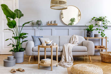 Stylish living room interior with design gray sofa, coffe table, rattan pouf, basket, shelf, mirror, tropical plants, decoration, carpet and elegant personal accessories in modern home decor.