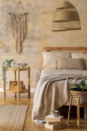 Stylish bedroom interior with design furniture, plant, rattan decoration and elegant personal accessories. Beautiful beige bed sheets, blanket and pillows. Template.