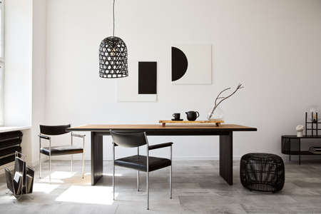 Stylish dining room interior with design wooden family table, black chairs, teapot with mug, mock up art paintings on the wall and elegant accessories in modern home decor. Template. Zdjęcie Seryjne