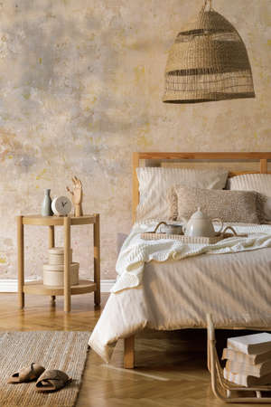 Stylish bedroom interior with design coffee table, furniture, carpet, rattan decoration, book and elegant personal accessories. Beautiful beige bed sheets, blanket and pillows. Template.