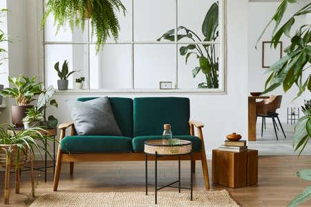 Stylish scandinavian living room interior with green velvet sofa, coffee table, carpet, plants, furniture, elegant accessories in modern home decor. Template. Foto de archivo
