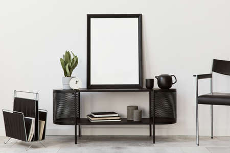 Interior design of modern living room with black stylish commode, chair, mock up poster frame, lamp, book, decorations and elegant accessories in home decor. Template.