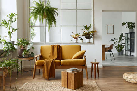 Interior design of scandinavian open space with yellow velvet sofa, plants, furniture, book, wooden cube and personal accessories in stylish home staging. Template.