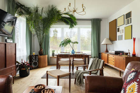 Modern scandinavian home interior of living room with design retro furniture, tropical plant, window, decoration and elegant personal accessoreis in stylish home decor.