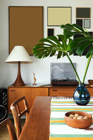 Stylish composition of home gallery wall at living room interior with tropical leaf in vase, table, cabinet, lamp and elegant decoration in modern home decor. Template.