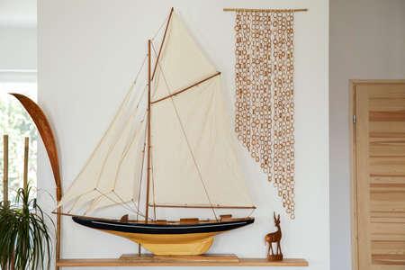 Stylish retro ship on the wooden shelf at living room interior. Home decor. Template. Reklamní fotografie