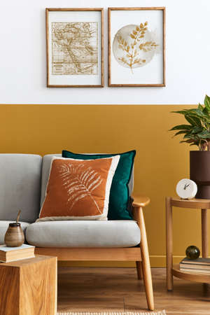 Interior design of modern living room with two mock up poster frames, elegant sofa, plant, pillow and personal accessories in stylish home staging. Honey yellow concept.
