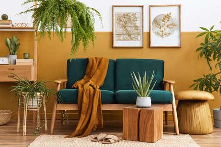 Stylish scandinavian interior of living room with design green velvet sofa, gold pouf, wooden furniture, plants, carpet, cube and mock up poster frames. Template. Reklamní fotografie