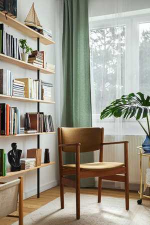 Stylish composition of home office interior with design retro chair, home library, plant, window, books, decoration and elegant personal accessories in home decor.