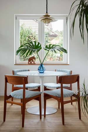 Stylish composition of dining room interior with design table, chairs, tropical leaf in vase, window and elegant decoration in home decor. Template.