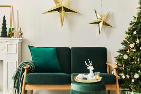 Stylish christmas living room interior with green sofa, white chimney, christmas tree and wreath, stars, gifts and decoration. Family time. Template.