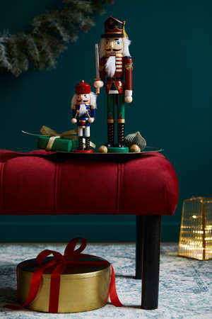 Christmas composition on the red velvet bench with decoration, gifts, wreath, nutcracker and accessories. Copy space. Red and green color. Template.