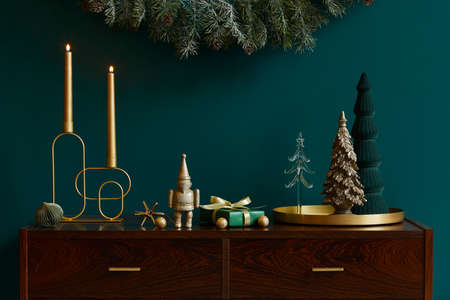Christmas composition on brwon wooden commode with decoration, christmas tree, gifts and accessories in cozy home decor. Copy space. Template. Reklamní fotografie