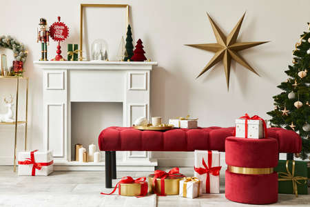 Stylish christmas composition at living room interior with white chimney, christmas tree and wreath, stars, gifts and decoration. Santa clause is coming. Template.