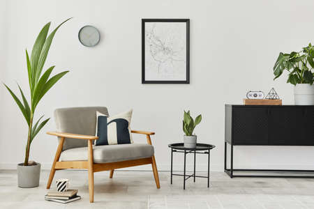 Modern retro concept of home interior with design gray armchair, coffee table, commode, plants, mock up poster map, carpet and personal accessoreis. Stylish home decor of living room.
