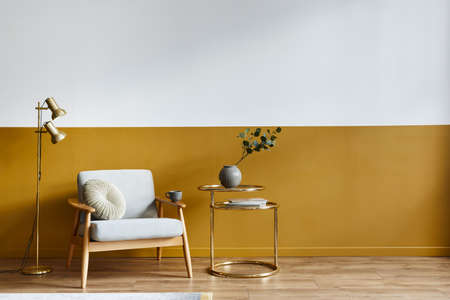 Unique living room in modern style interior with design armchair, elegant gold coffee table, copy space, flowers in vase, decoration and pesronal accessories in home decor. Template. 版權商用圖片