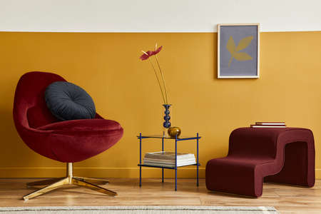 Unique living room in modern style interior with mock up poster frame, design red velvet armchair, elegant furniture, decoration and pesronal accessories in home decor. Honey yellow wall. Template.