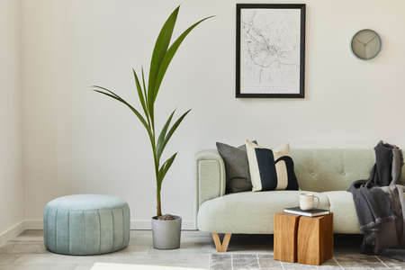 Unique loft interior with green comfortable sofa, design furniture, mock up poster map, carpet, plants, decoration and elegant accessories. Modern home decor in living room. White wall. Template.