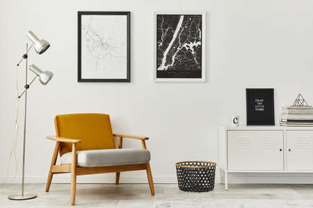 Retro and minimalist compositon of living room interior with design armchair, two mock up poster map, lamp, decoration, white wall and personal accessories. Template. Modern home decor. 版權商用圖片 - 160551215