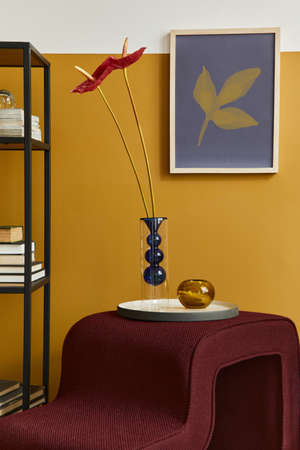 Stylish compositon in modern living room interior with design stool, vase with flower, bookcase and mock up poster frame. Yellow wall. Template. 版權商用圖片