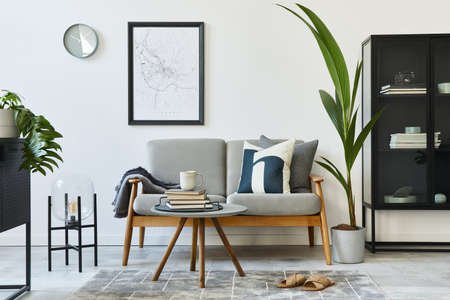 Modern retro concept of home interior with design gray sofa, coffee table, plants, furniture, mock up poster map, decoration and personal accessoreis. Stylish home decor of living room.