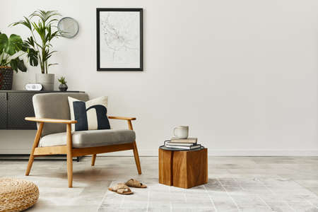 Modern retro concept of home interior with design gray armchair, coffee table, plants, mock up poster map, carpet and personal accessoreis. Stylish home decor of living room.