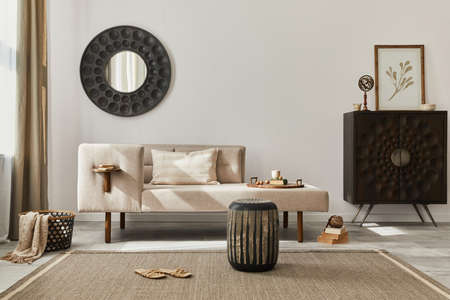 Interior design of ethnic style living room with modern commode, round mirror, decoration, furniture and personal accessories. Template. White wall. 版權商用圖片 - 160681784