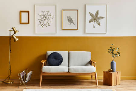 Unique living room in modern style interior with design sofa, elegant wooden cube, mock up poster, lamp, frames, flowers in vase, decoration and pesronal accessories in home decor. Template.