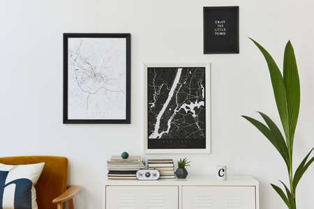 Retro modern compositon of living room interior with design armchair, two mock up poster map, clock, plant, decoration, white wall and personal accessories. Template.