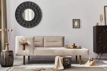 Interior design of ethnic style living room with modern commode, round mirror, decoration, furniture and personal accessories. Template. White wall.