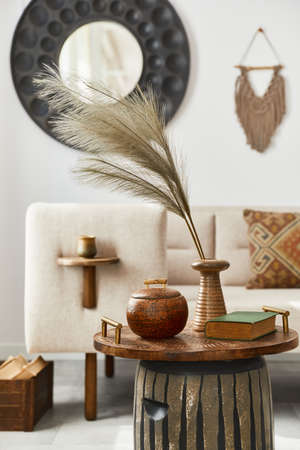 Elegant ethnic composition of living room interior with design coffee table, sofa, decoration, mock up frame and acceessories in modern home decor. Template. Details. 版權商用圖片