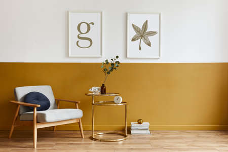 Unique living room in modern style interior with design armchair, elegant gold coffee table, mock up poster frames, flowers in vase, decoration and pesronal accessories in home decor. Template. 版權商用圖片