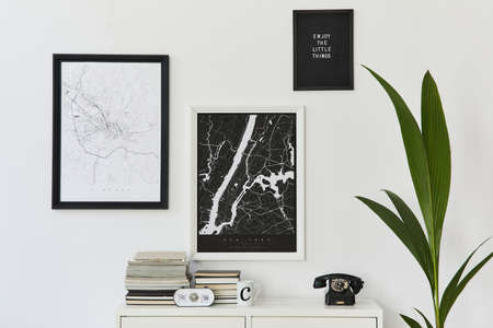 Modern and minimalist concept of two mock up poster maps with white commode, decoration, book, plant, clock and elegant personal accessories. Template.