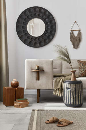 Elegant ethnic composition of living room interior with design coffee table, sofa, decoration, flowers in vase and acceessories in modern home decor. Template. Details.