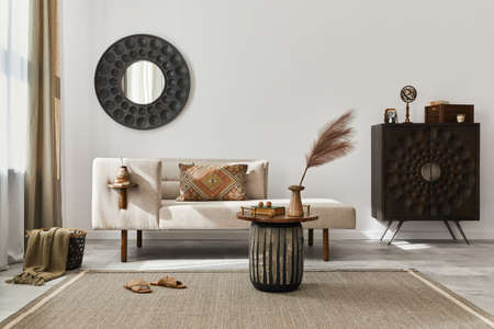 Interior design of ethnic living room with modern commode, round mirror, decoration, furniture and personal accessories. Template. White wall.