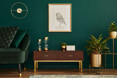 Luxury interior with stylish velvet sofa, wooden commode, mock up poster frame, plants, gold decoration and elegant personal accessories. Modern living room in classic house. Template.