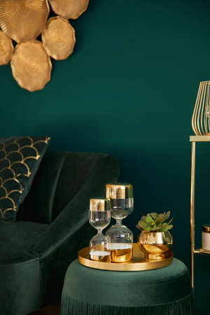 Vertical photo of elegant living room with green velvet pouf, gold decor, design hourglass, sofa and elegant accessories. Element of luxury interior at cozy house. Template.