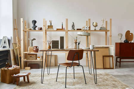Unique artist workspace interior with stylish desk, wooden easel, bookcase, artworks, painting accessories, decoration and elegant personal stuff. Modern work room for artist. Template. 版權商用圖片 - 164634872